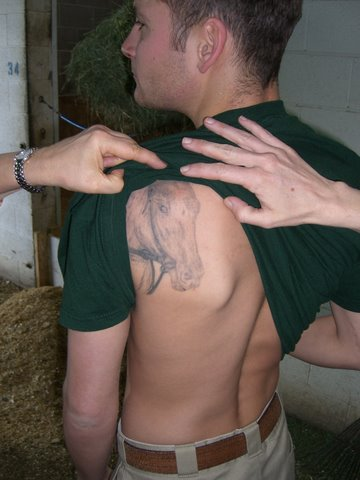 Dominick, the exercise rider, who is in the midst of getting a tattoo of Rachel on his back.